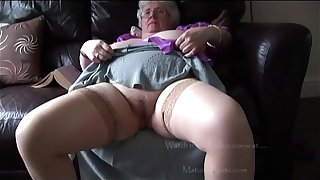 Mature granny with massive tits and hairy bush stripping and teasing